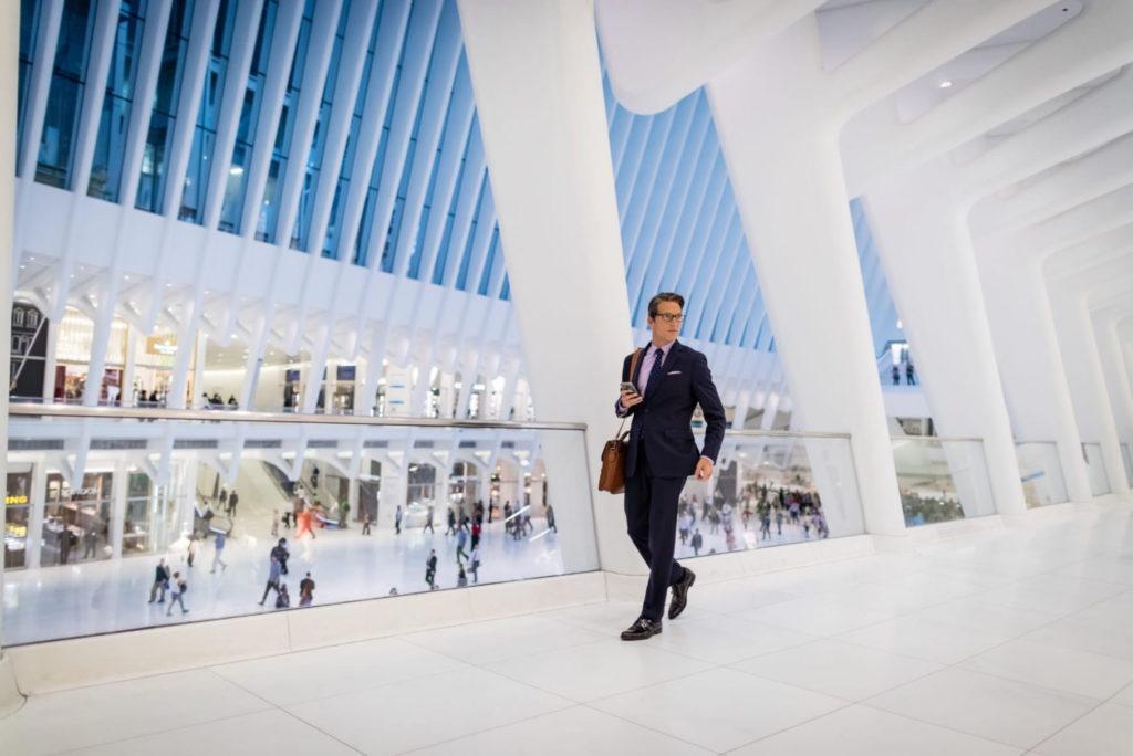 man in suit walking through oculus path station downtown