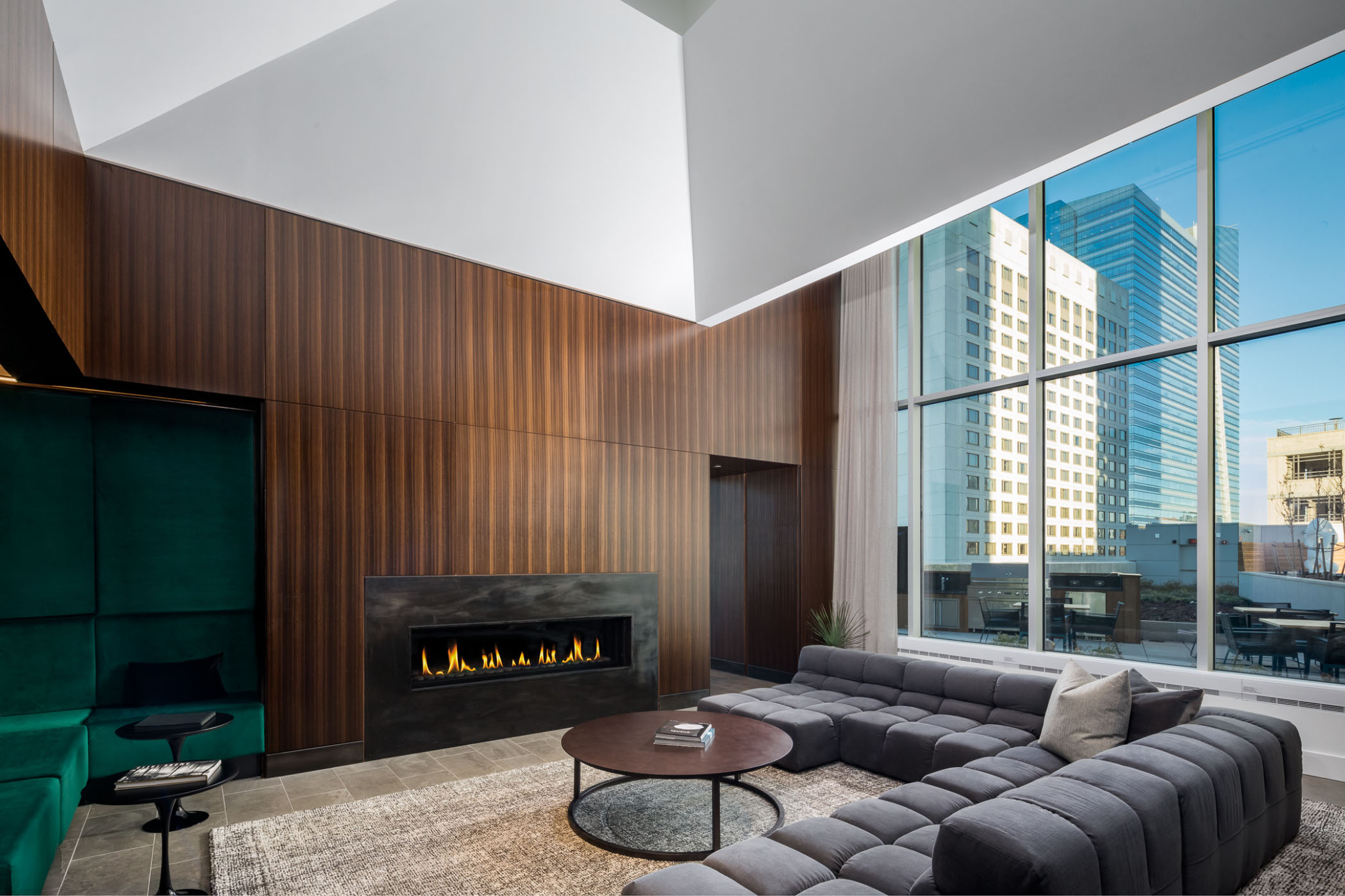 resident lounge with giant wall of window fire place and luxury gray couch