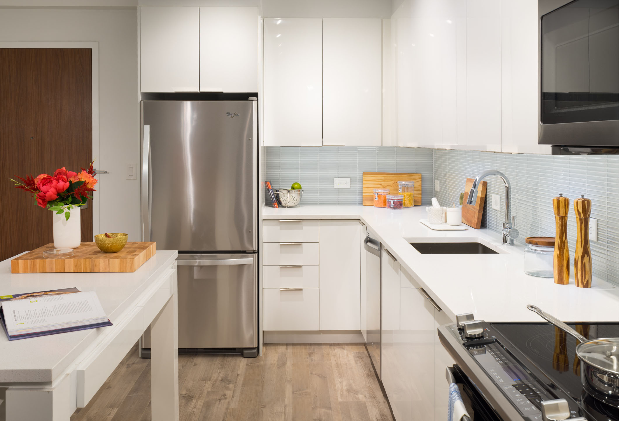 all white kitchen with stainless steel appliances in new luxury vyv