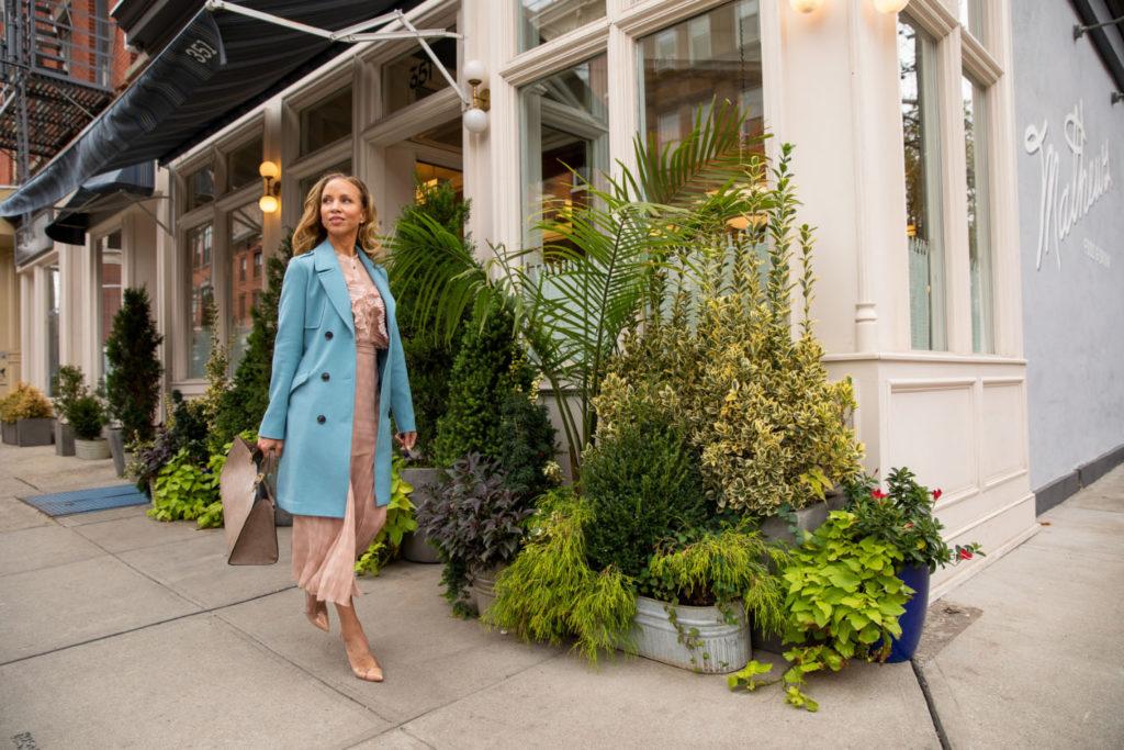 woman in blue jacket walking by matthews restaurant jersey city